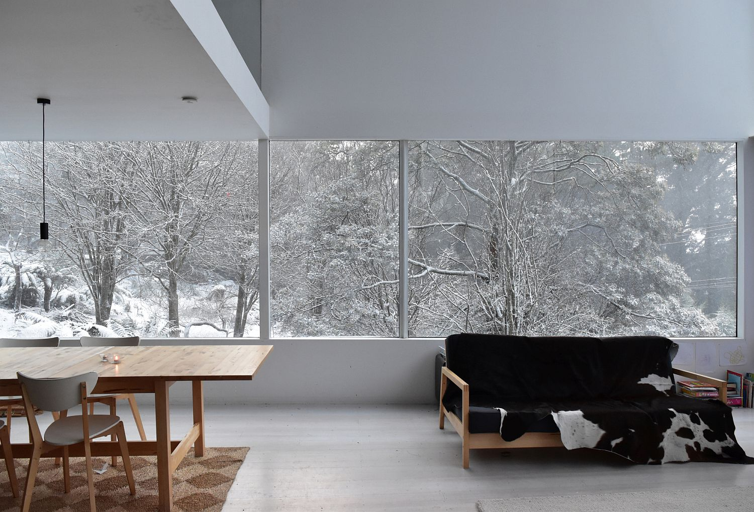 White dining space of the house with a view of the snow-clad landscape outside