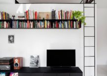 White-wall-of-the-living-roomw-ith-metallic-shelving-in-black-217x155