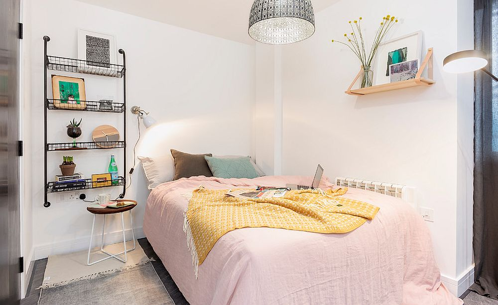 Bedding brings pastel pink to the small Scandinavian bedroom