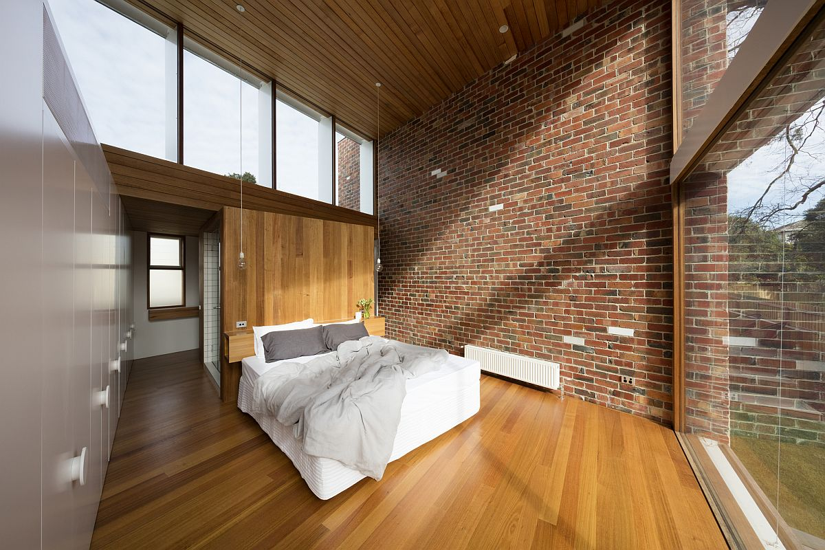 Brick walls and wooden ceiling for the contemporary bedroom with park views