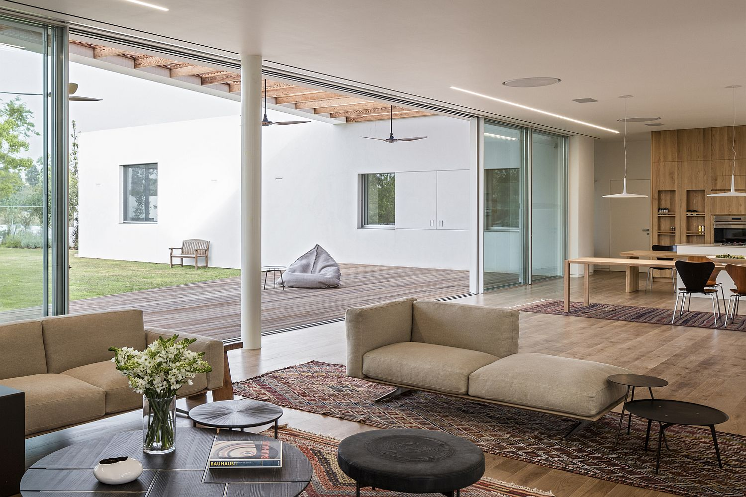 Bright and cheerful modern living room connected with the pergola covered deck