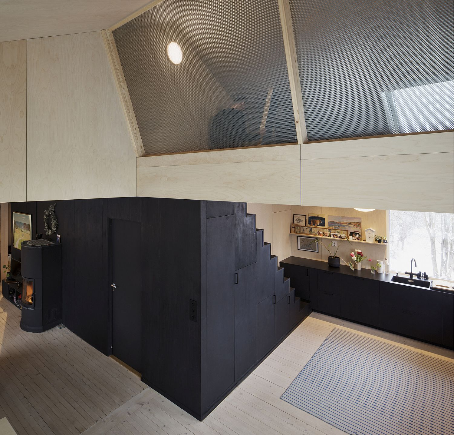 Dark stairway with built-in storage leeds to the space-savvy attic level