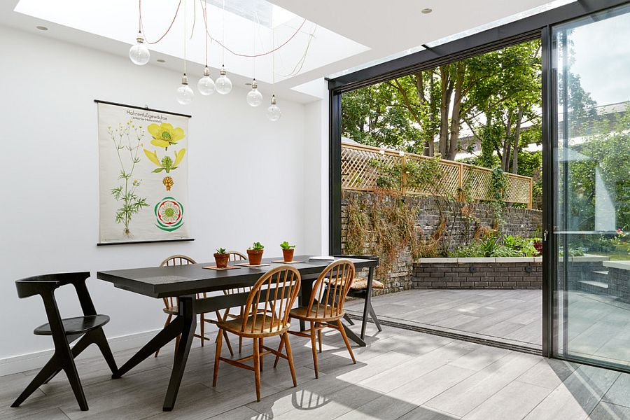 Elegant kitchen in white connected to the garden uses botanical art to bring greenery indoors