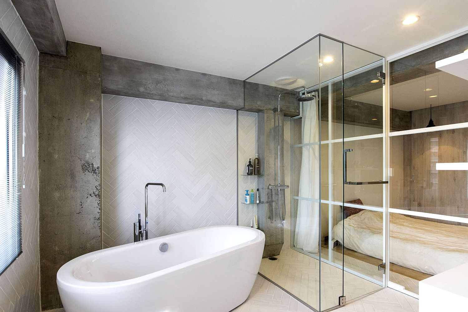 Exposed-concrete-finishes-combined-with-herringbone-pattern-backsplash-and-glass-shower-cube