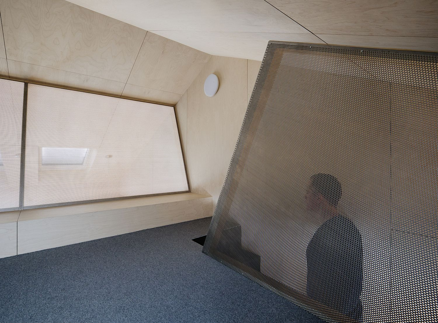 Half-transparent perforated steel panels used for the attic level