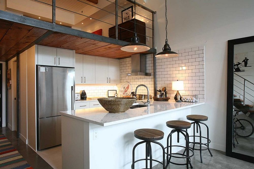 Industrial style kitchen with a simple mezzanine level above that overlooks the living area