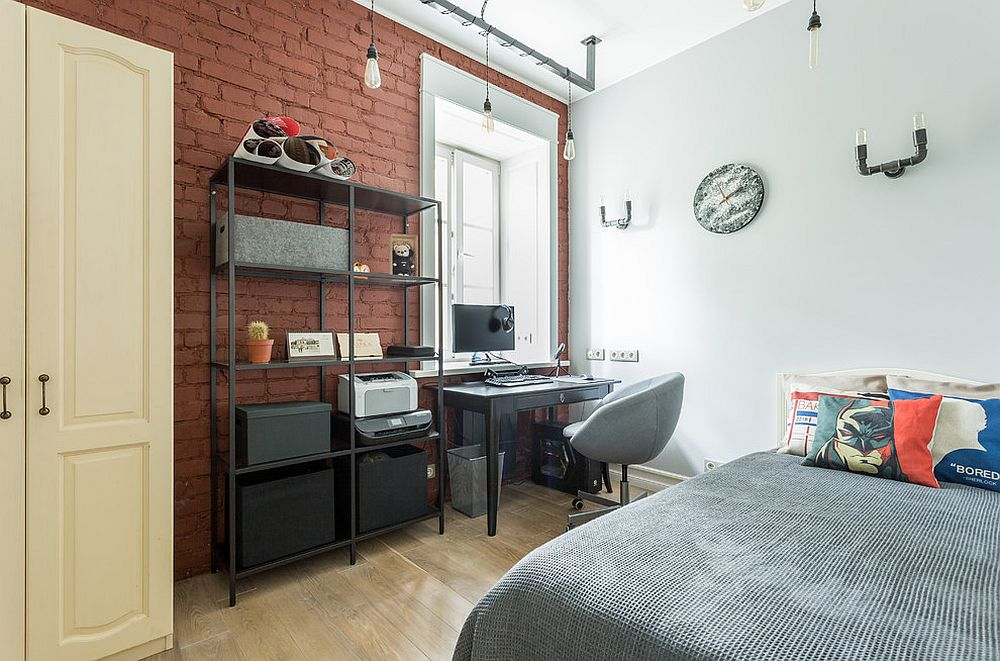 Light-filled industrial kids' room with accent brick wall
