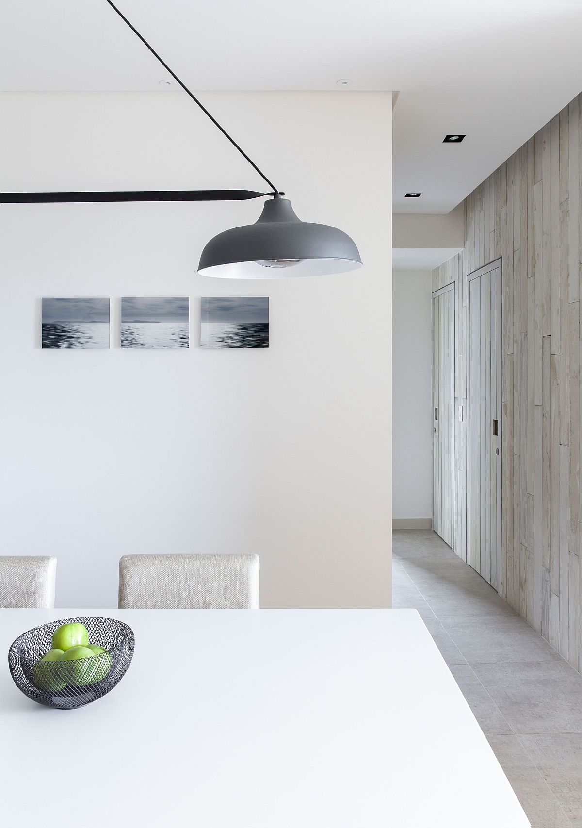 Minimal and modern dining room in white with gray pendant lighting