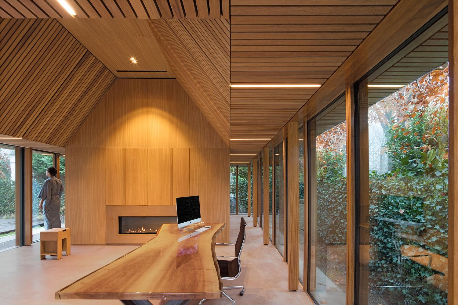 Natural edge work desk and an interior draped in Irok wood create a cozy office