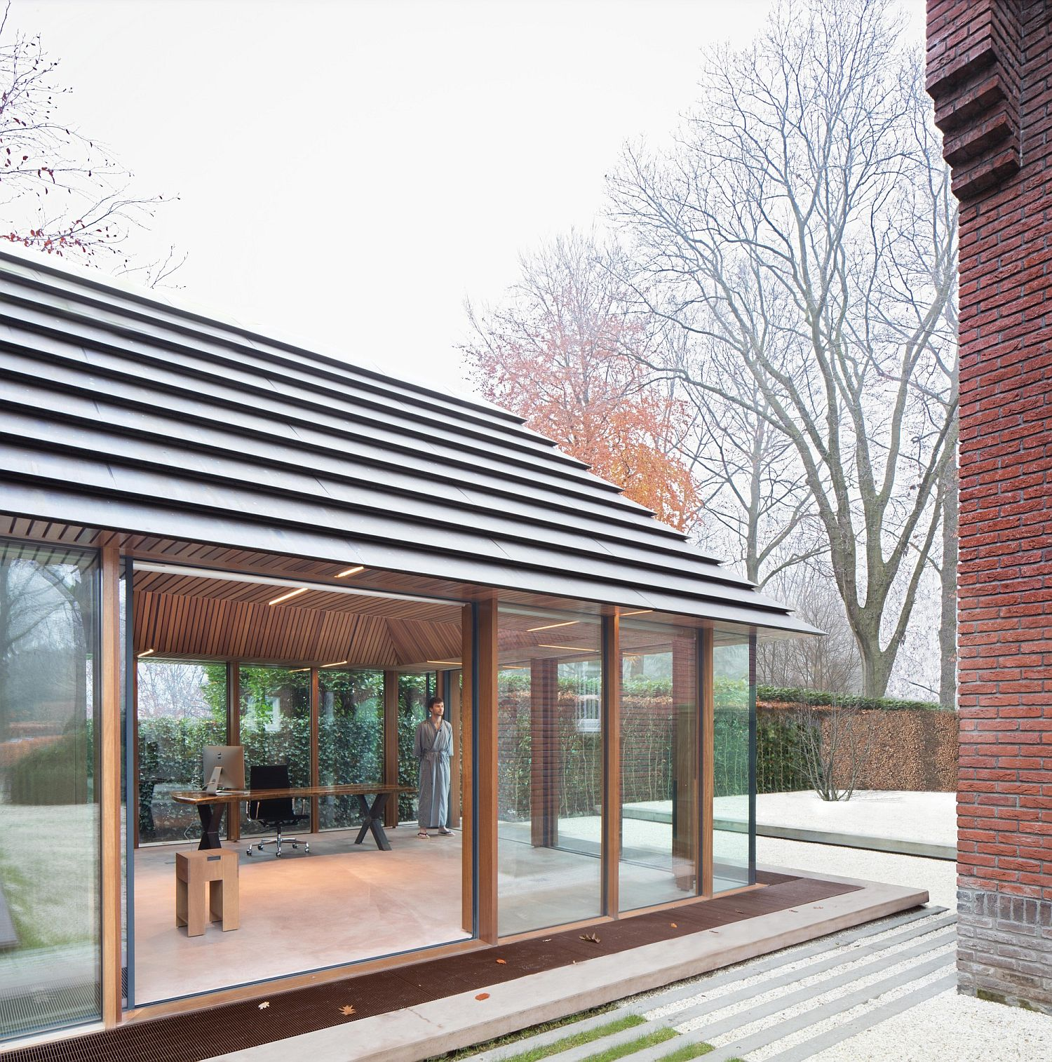 Tiny Office Pavilion Vught sits next to a classic Dutch home with red brick exterior
