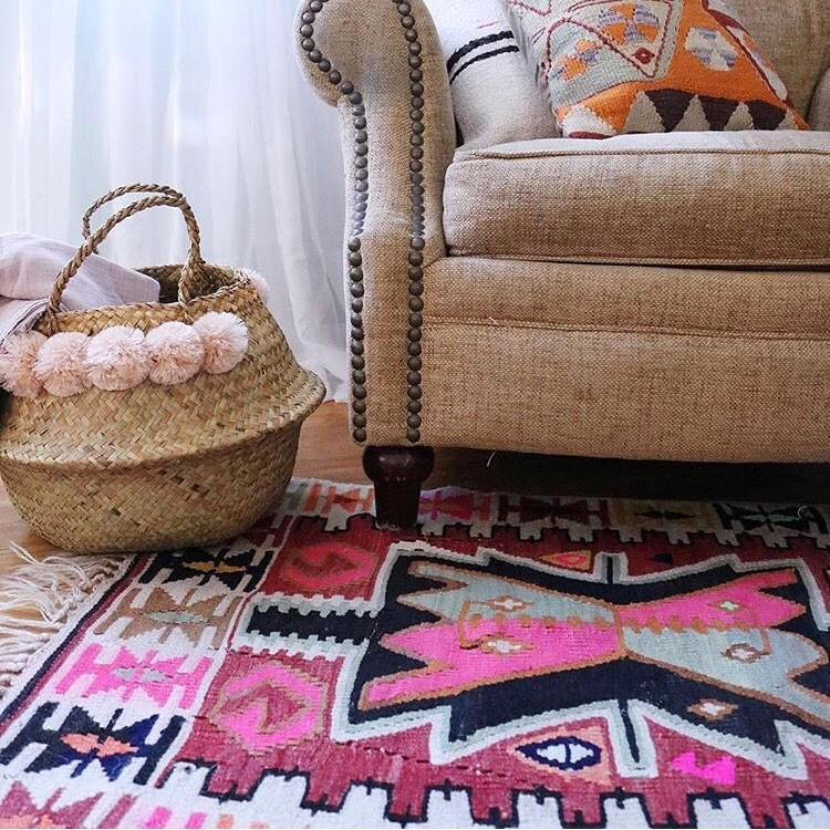 A-seagrass-belly-basket-with-blush-pom-poms
