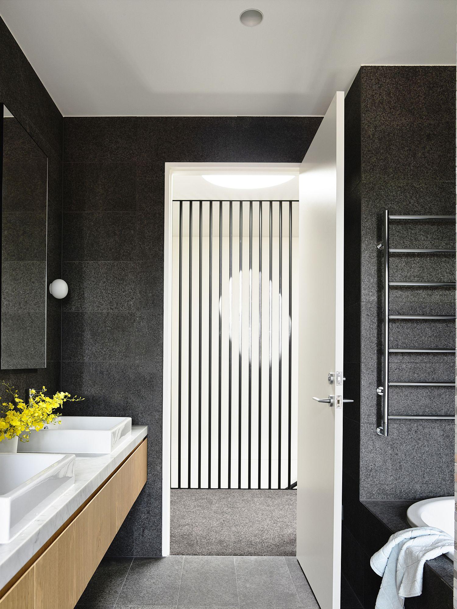 Bathroom combines dark walls with light wood vanity and stone countertop