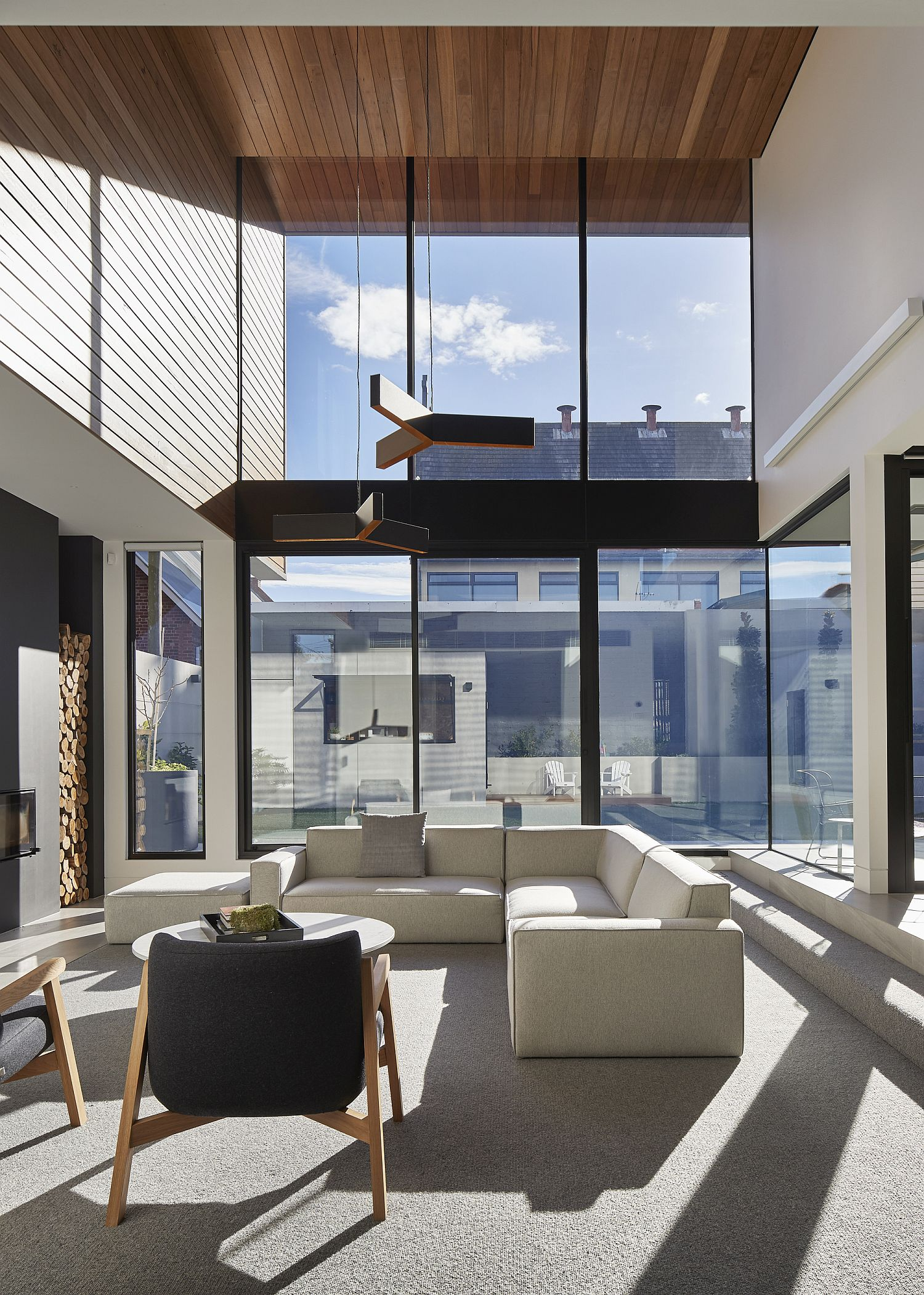 Dark-metallic-frame-glass-windows-and-a-wooden-roof-give-the-interior-a-unique-look