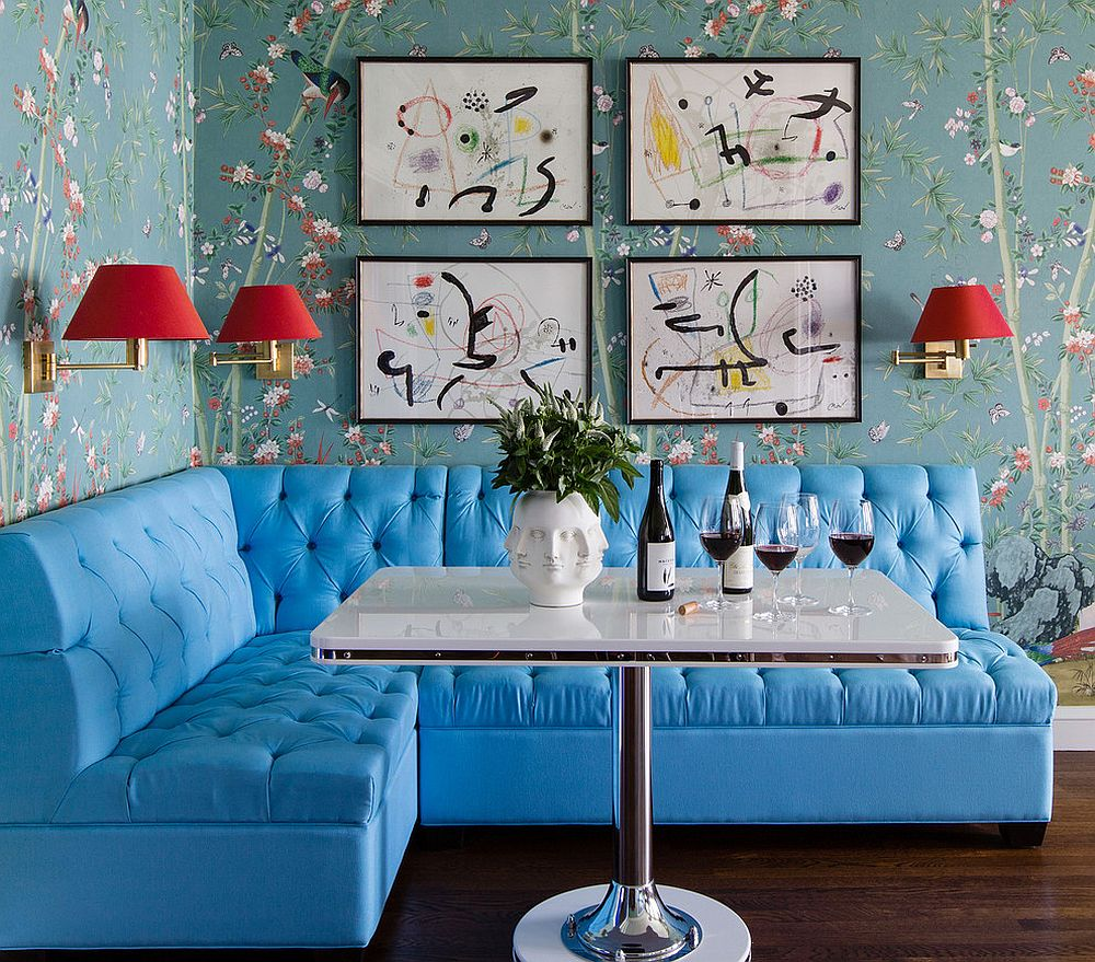 Eclectic dining room with a wallpapered backdrop, simple collection of prints and banquette seating