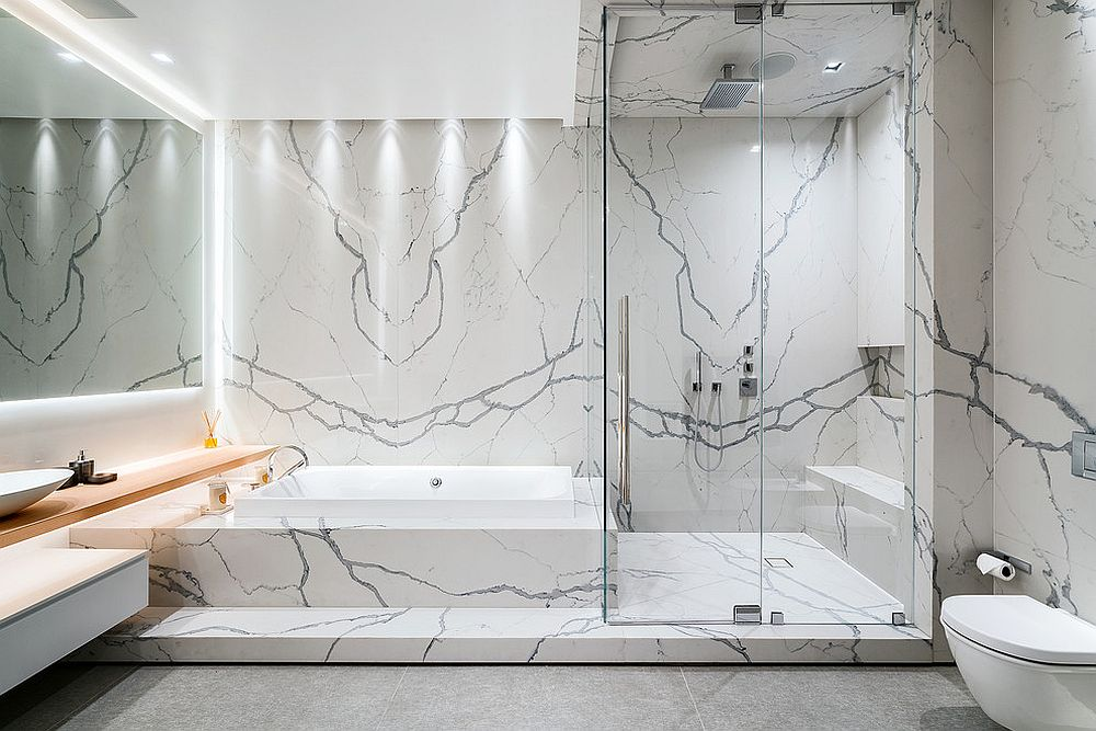 Even a hint of wood brings warmth to the contemporary minimal bathroom covered in marble