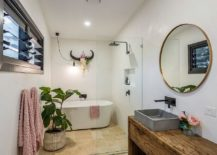 Evenly-lit-white-bathroom-with-a-wooden-vanity-and-round-mirror-217x155