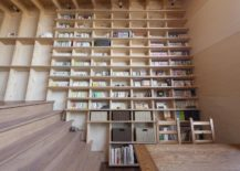 Large-oblique-wall-serves-as-a-giant-bookshelf-in-the-living-area-217x155