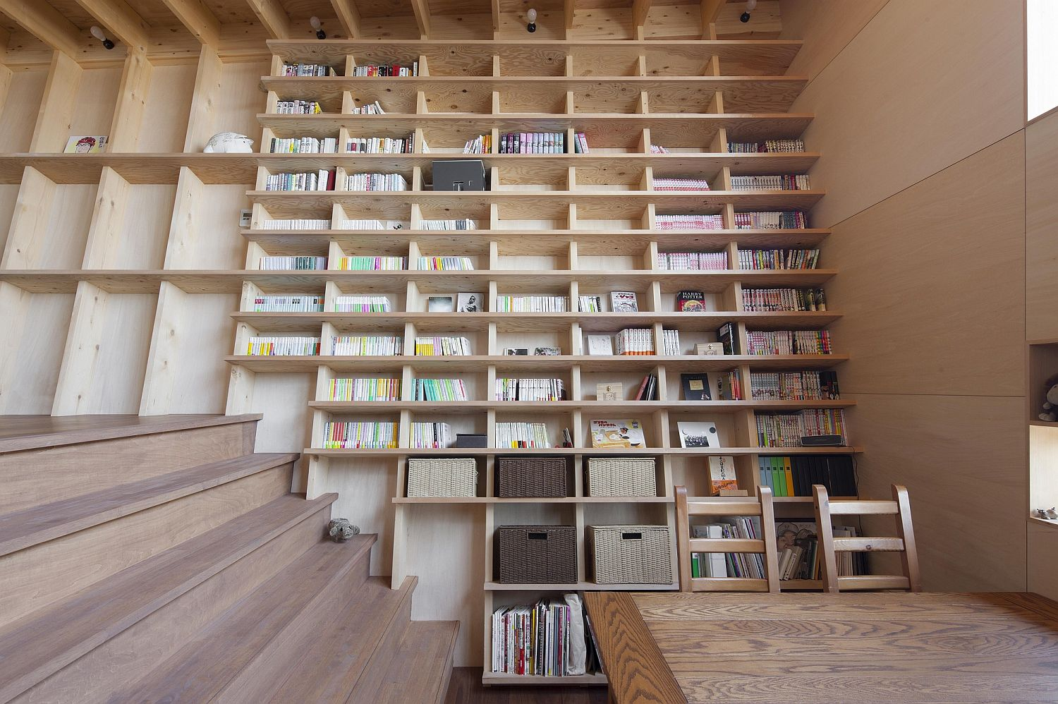 Large oblique wall serves as a giant bookshelf in the living area