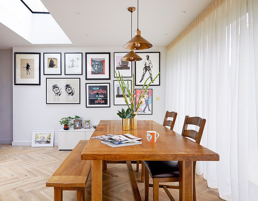 Transitional dining room in white with a wooden table and gallery wall