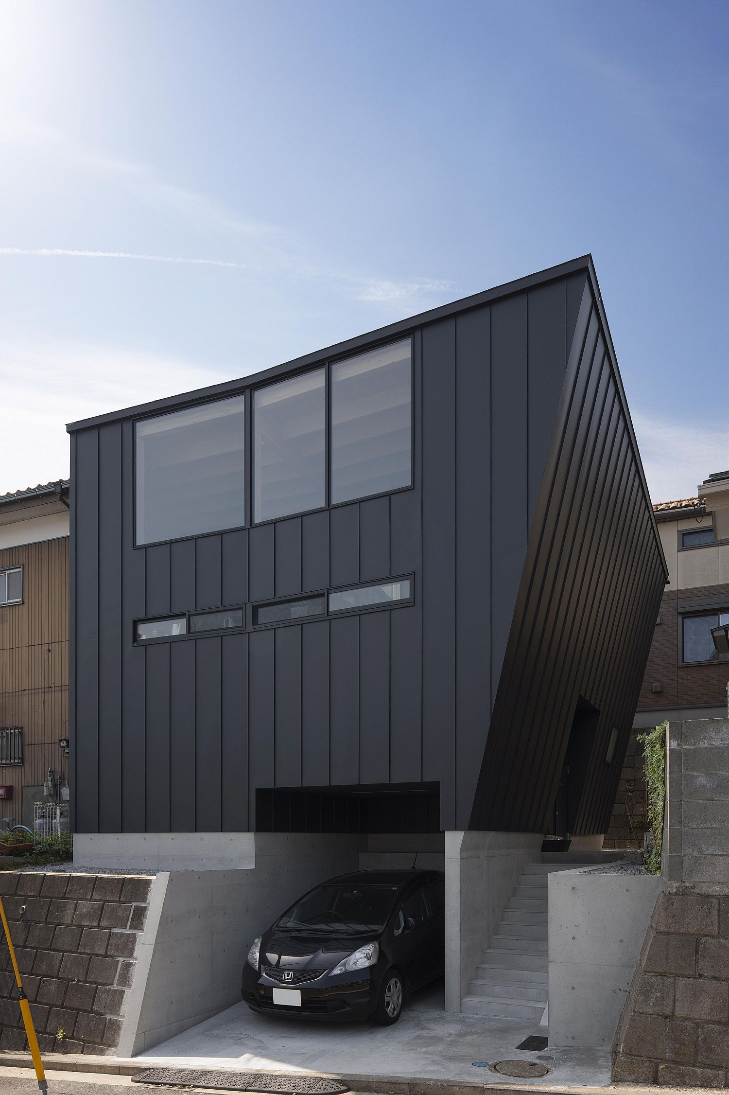 Unique facade of the Japanese home in black with carport