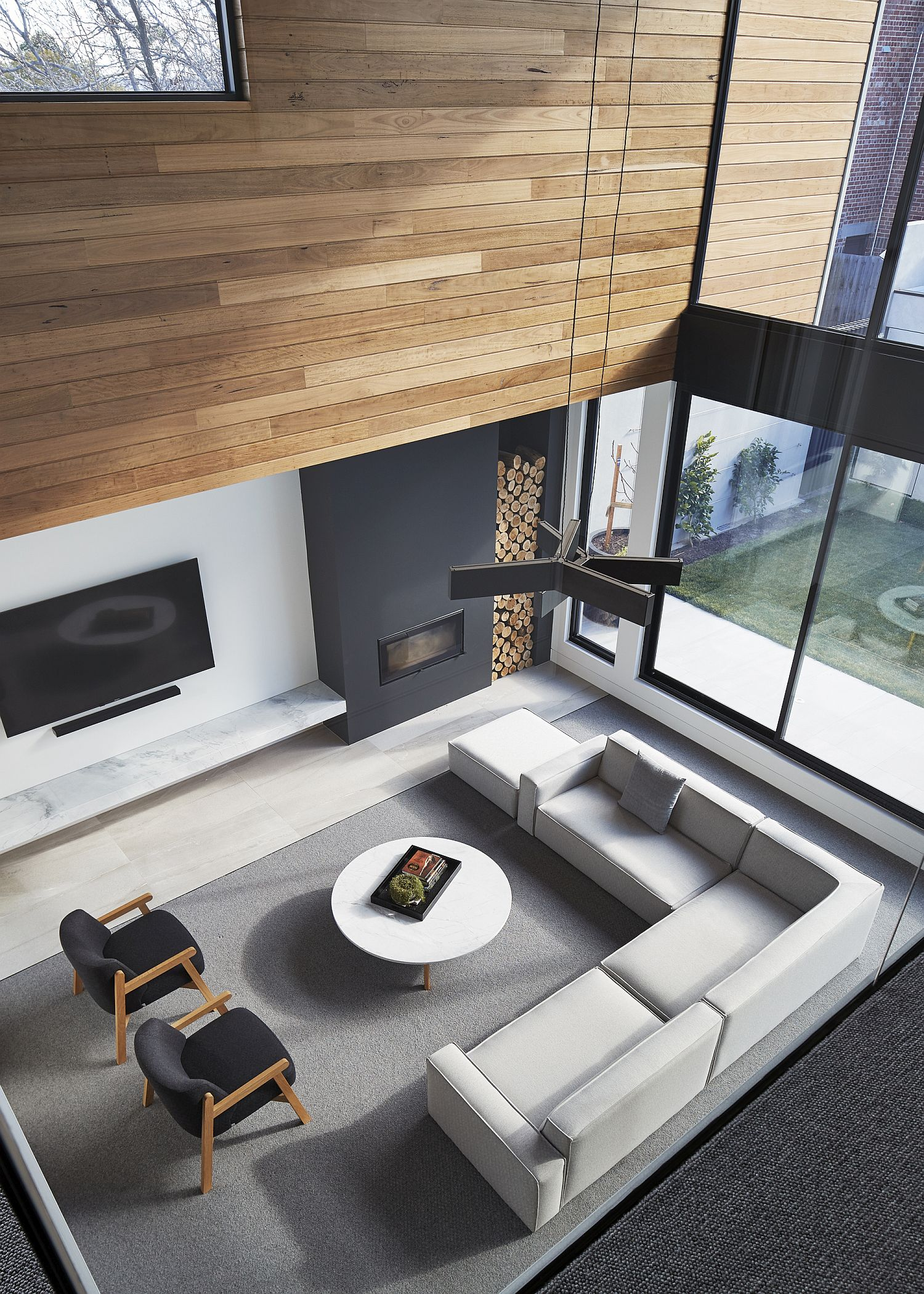 View-of-the-double-height-living-area-with-gray-fireplace-and-slim-TV-unit