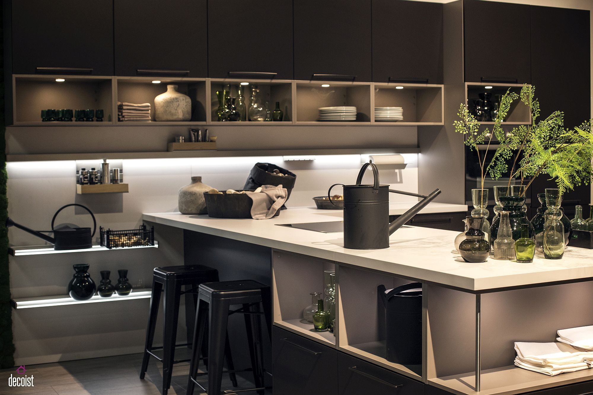Black kitchen island with white countertop and open shelving