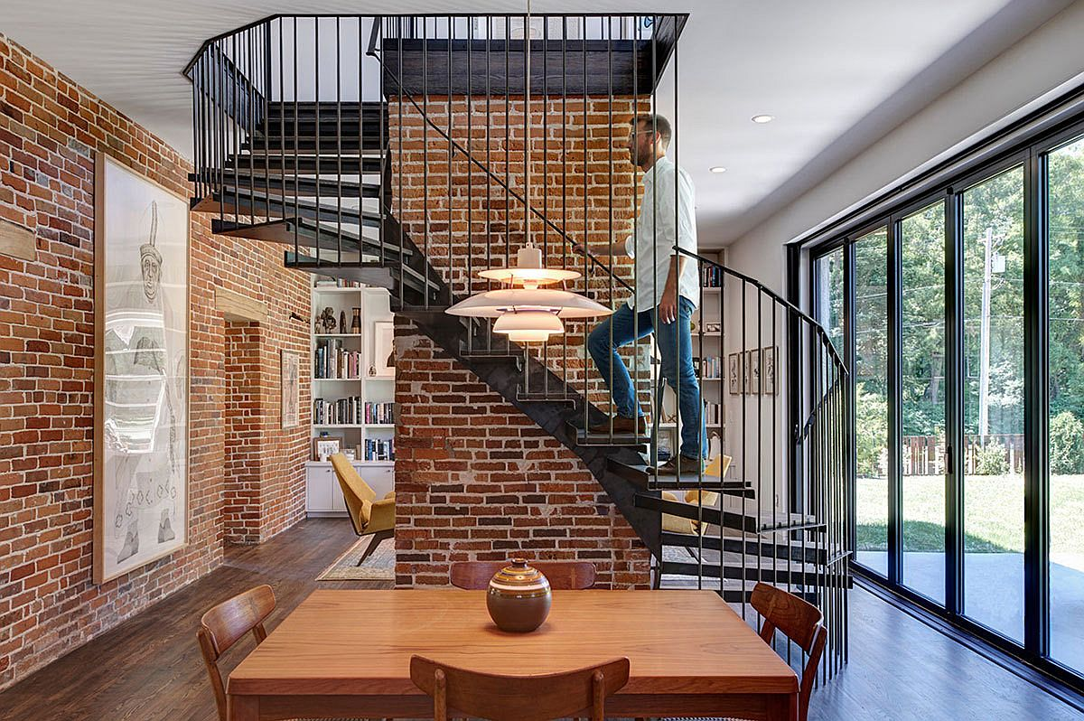 Brick wall in the backdrop along with stylish spiral stairway give the interior an industrial vibe