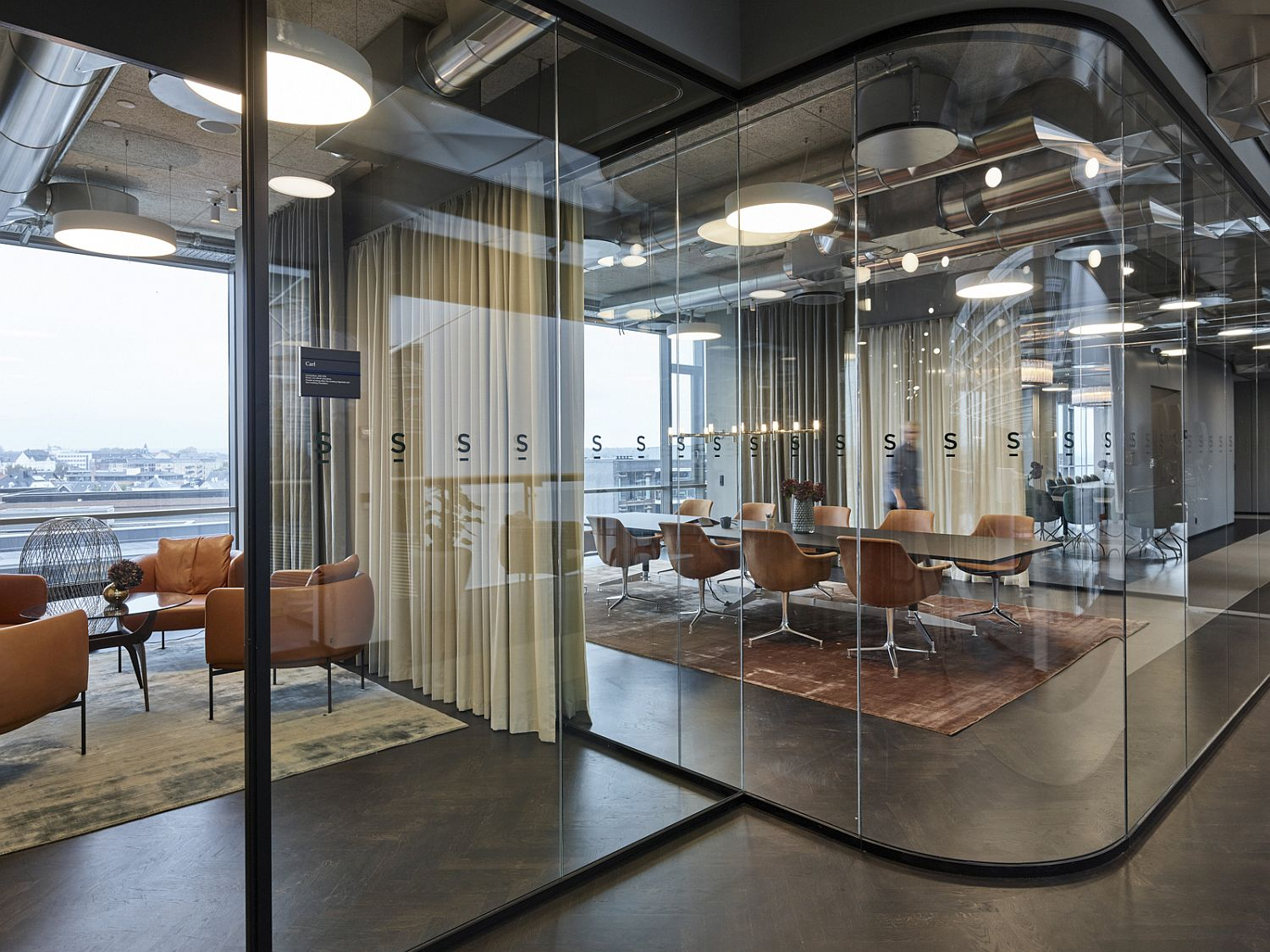 Glass cubes and cubicles throughout the office create a tranquil, yet social work environment