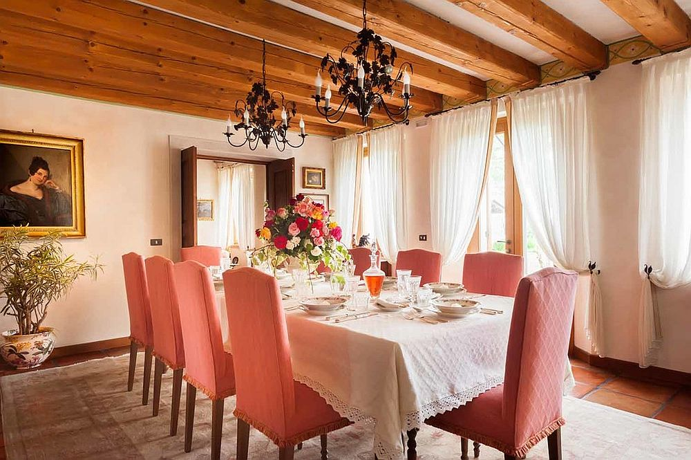 Gorgeous Mediterranean dining room with wooden ceiling beams and pastel pink chairs