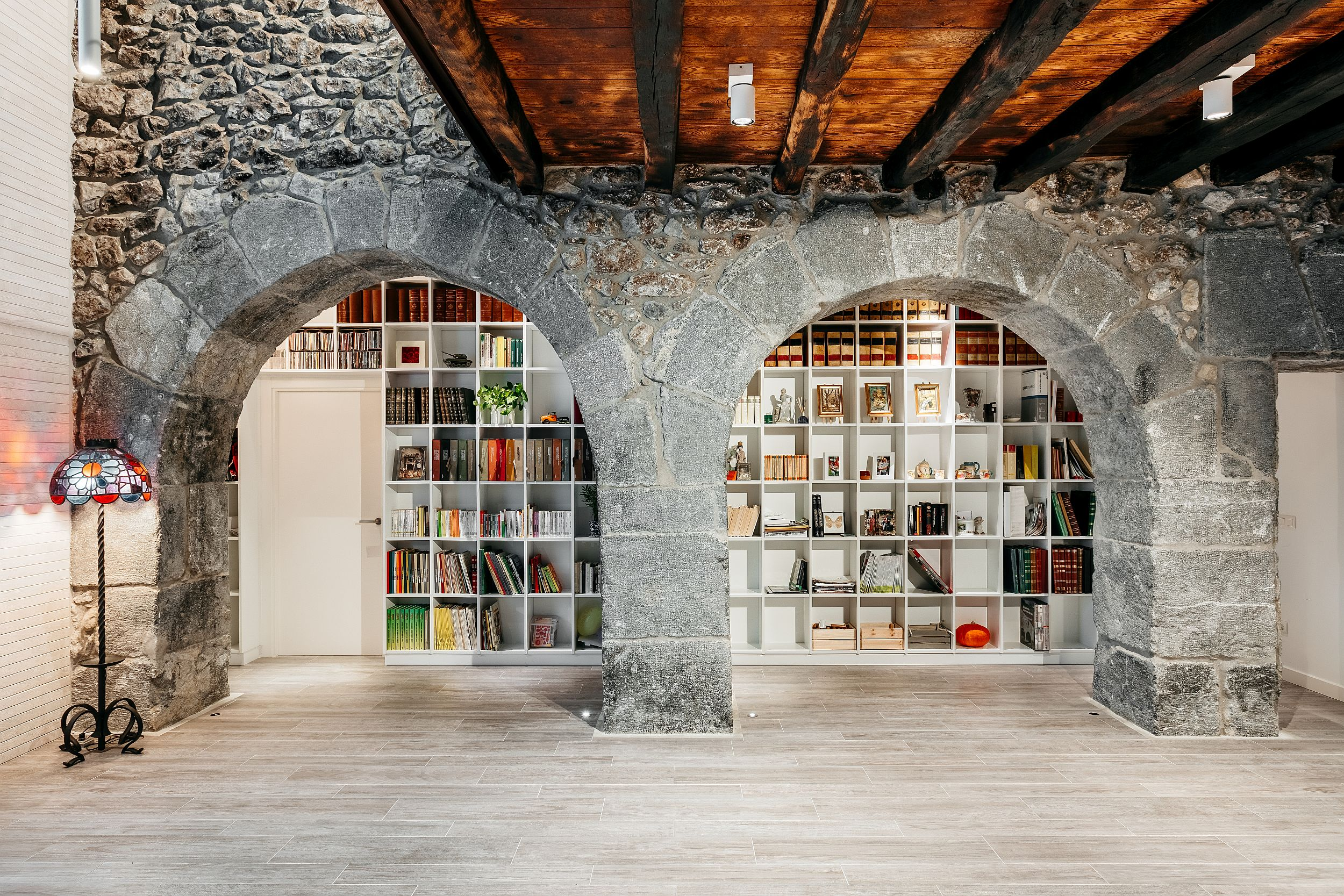 Historic stone walls inside the house combined with modern bookshelves
