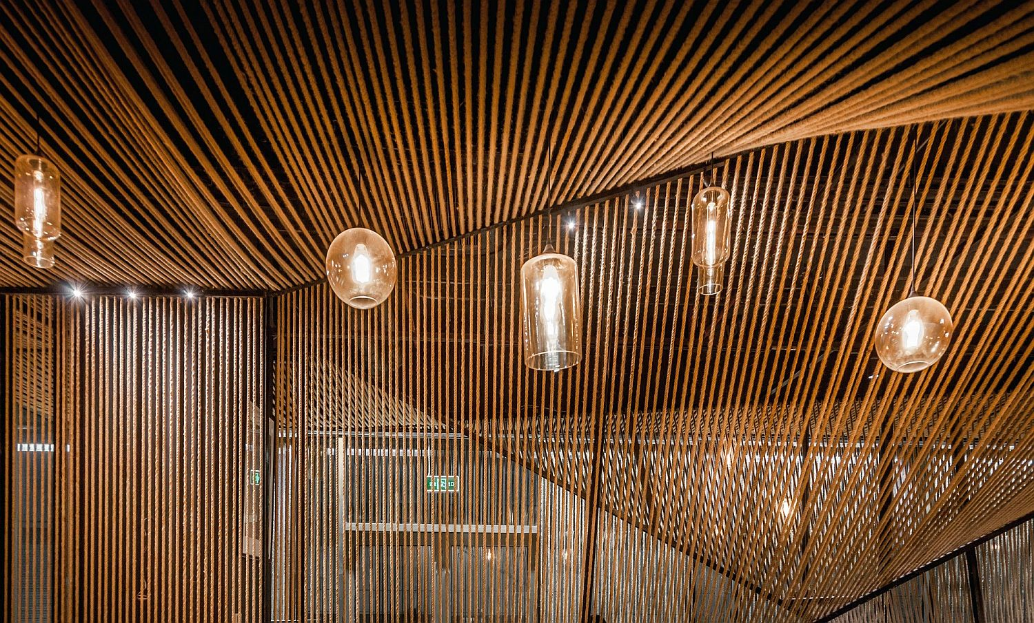 Lighting and rope combine to hide ceiling beams and other structural forms