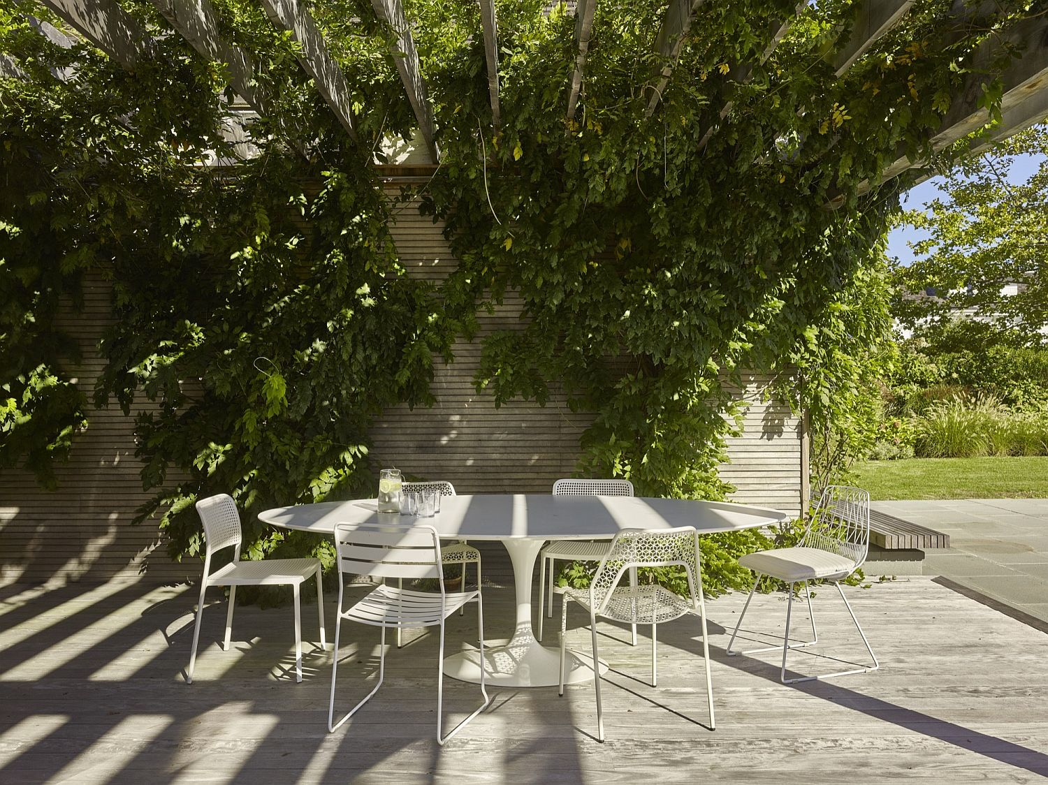 Lovely outdoor dining area with greenery above offering ample shade