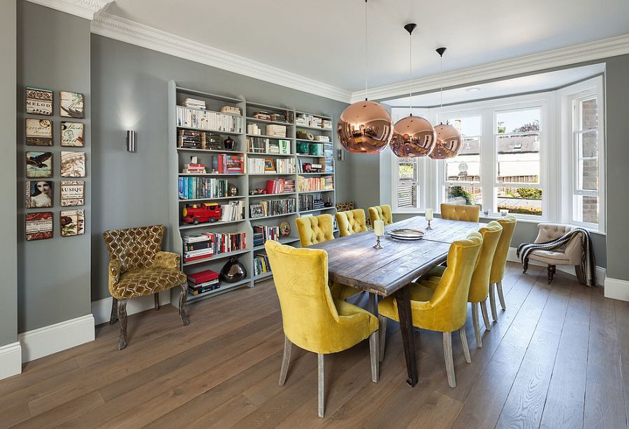 Lovely yellow chairs bring sunshine to the gray dining room