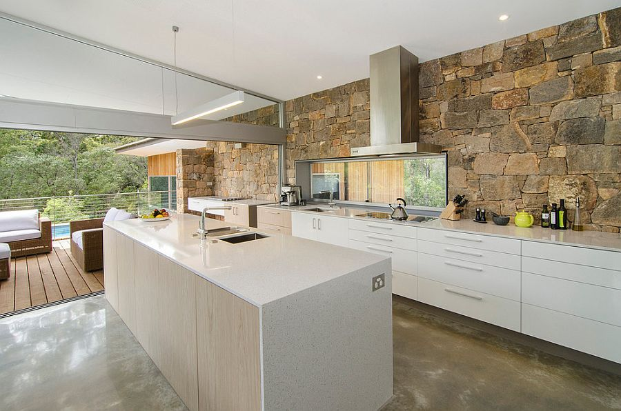 Modern kitchen with stone wall in the backdrop