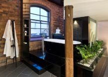 Refined-finishes-coupled-with-exposed-brick-walls-inside-the-industrial-bathroom-217x155