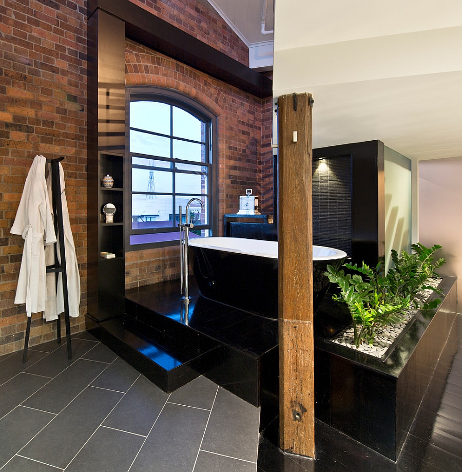 Refined finishes coupled with exposed brick walls inside the industrial bathroom