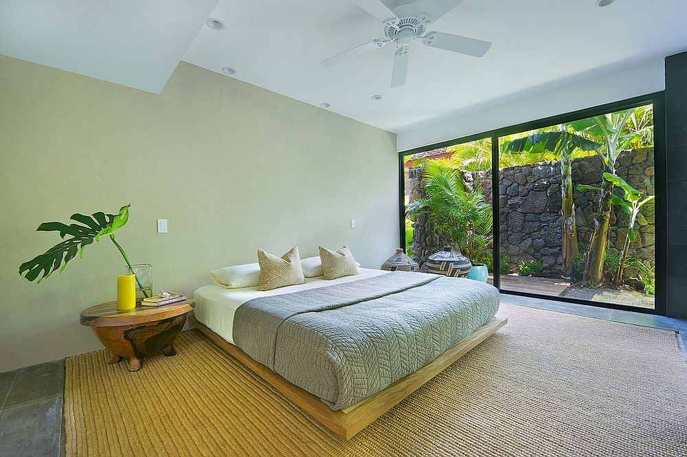 Stone wall and garden outside give the bedroom a tropical flavor
