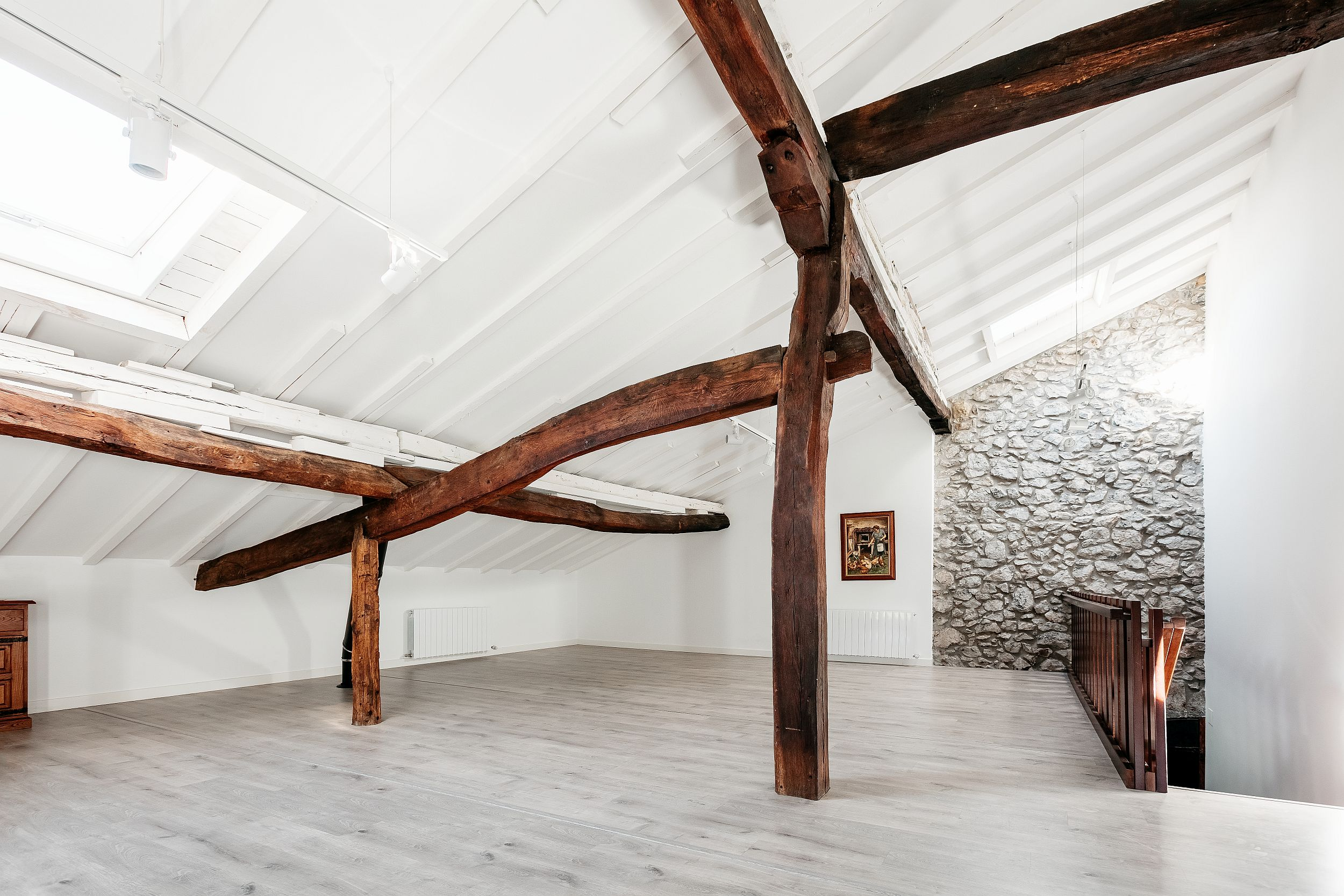 Structural wooden beams on the attic level have beeb used elegantly to create a modern traditional confluence