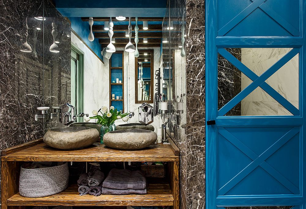 Unique industrial bathroom in stone with wooden vanity and blue backdrop