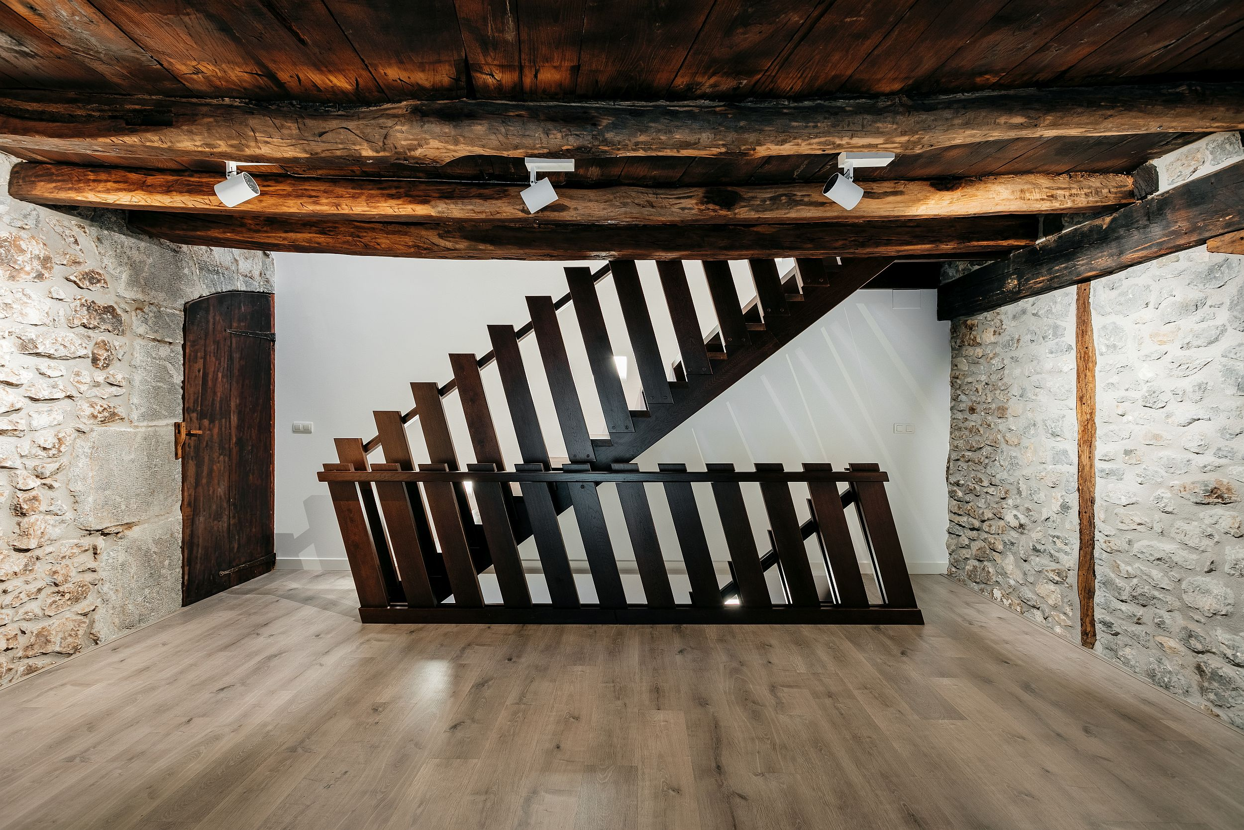 Weathered walls, ceiling beams and metal staircase usher in plenty of textural contrast