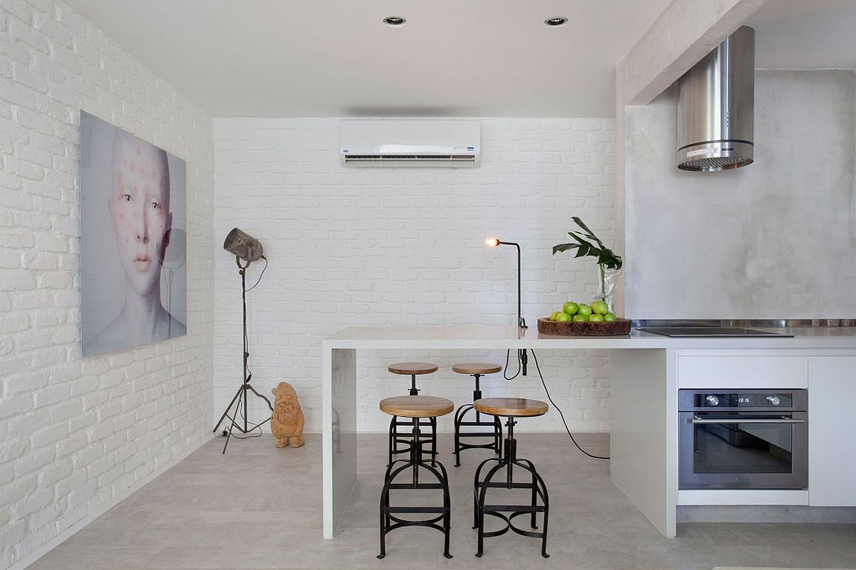 Bar stools and painted brick walls bring textural charm to the small kitchen