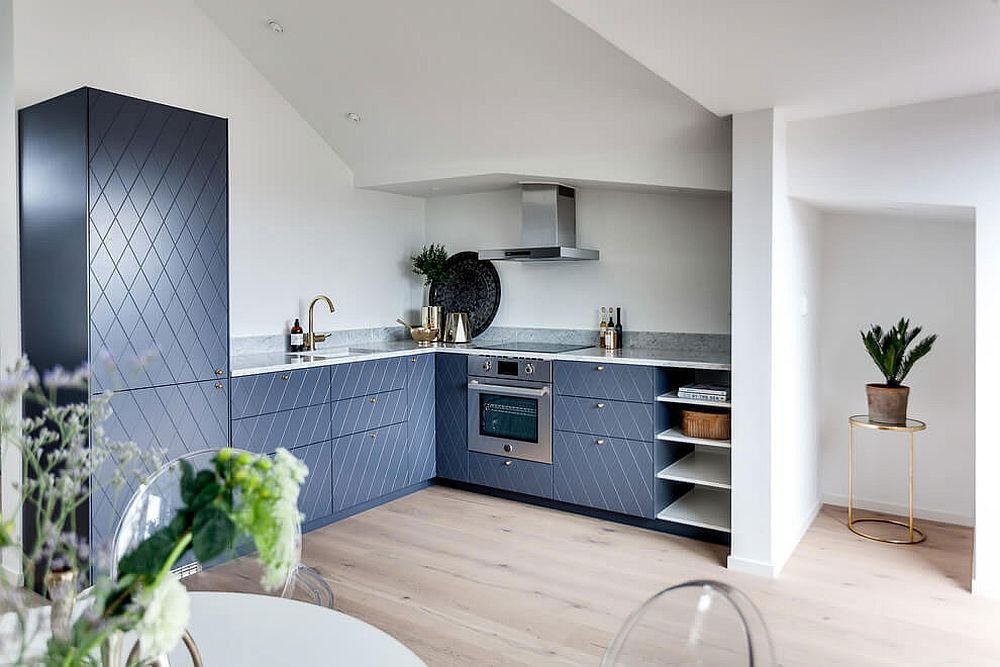 Brilliant blue patterened cabinets shape this brilliant corner kitchen inside the Scandinavian apartment