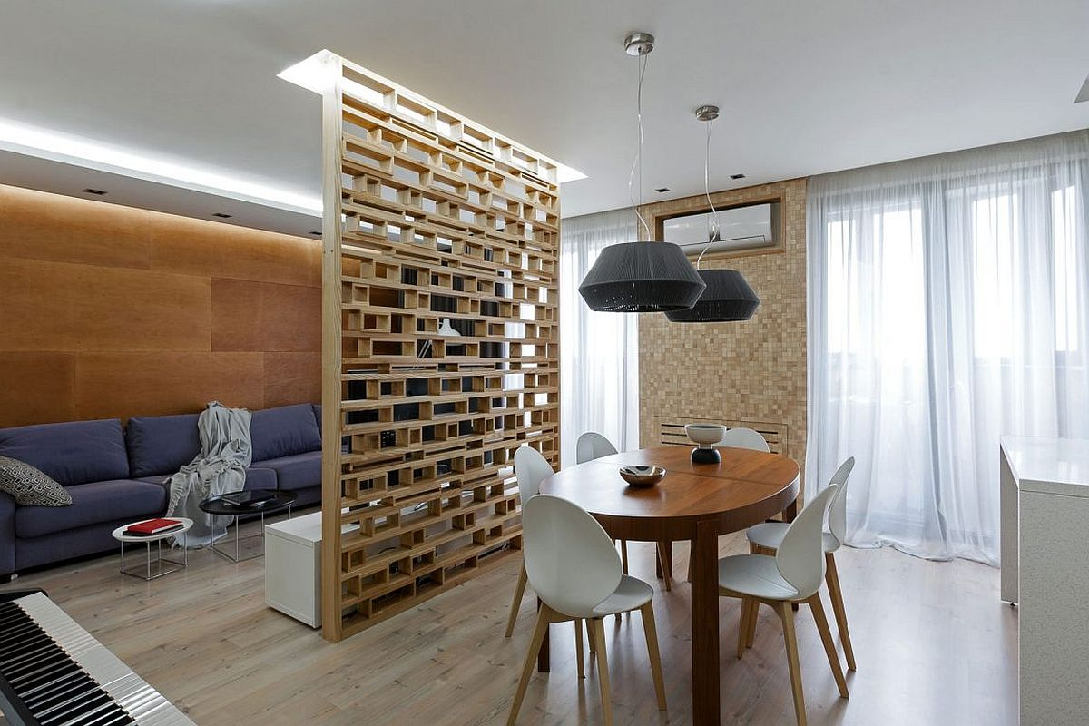 Custom plywood partition delineates living room from the dining area in this small apartment