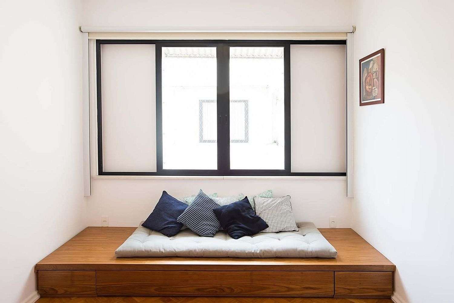 Elevated platform next to the window provides great space for a minimal bed
