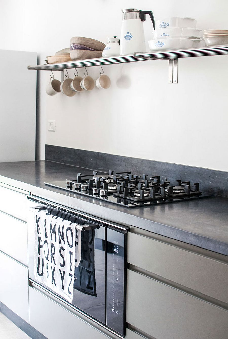 Floating shelves and hooks on the walls help save further space in the tiny kitchen