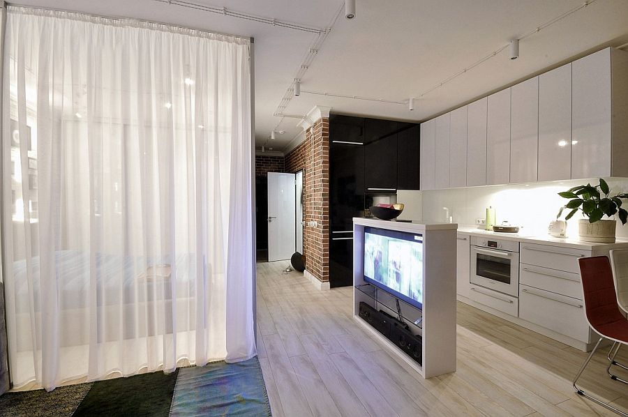Freestanding TV station delineates the bedroom and living space from the single-wall kitchen