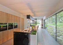 Large-floor-to-ceiling-glass-windows-offer-panoramic-views-of-the-forest-from-the-kitchen-217x155