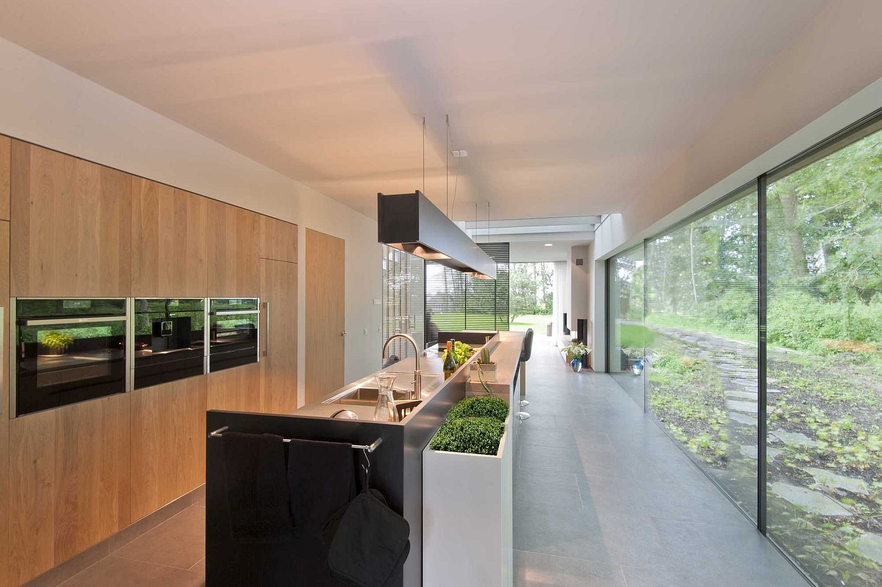 Large floor-to-ceiling glass windows offer panoramic views of the forest from the kitchen