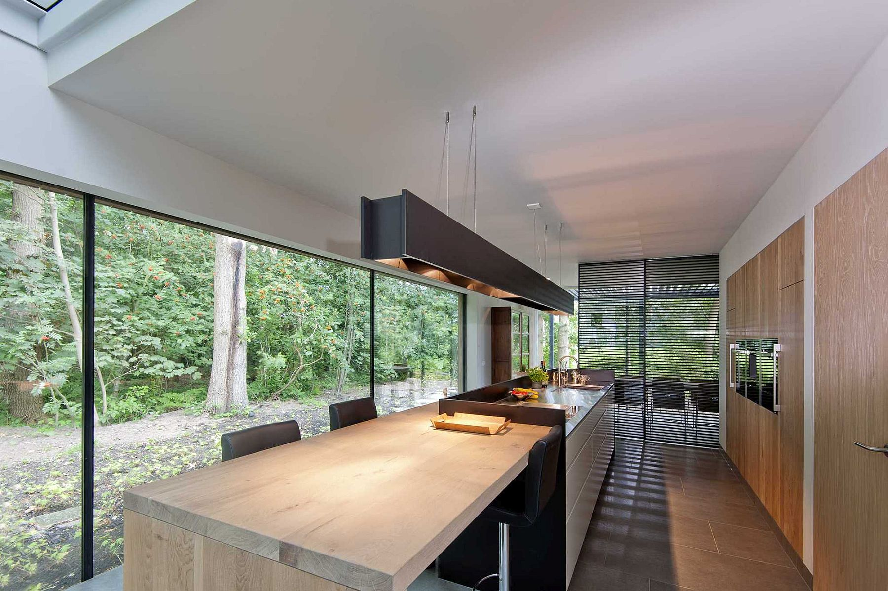 Long kitchen island in black with a cool wooden breakfast nook and dining zone next to it