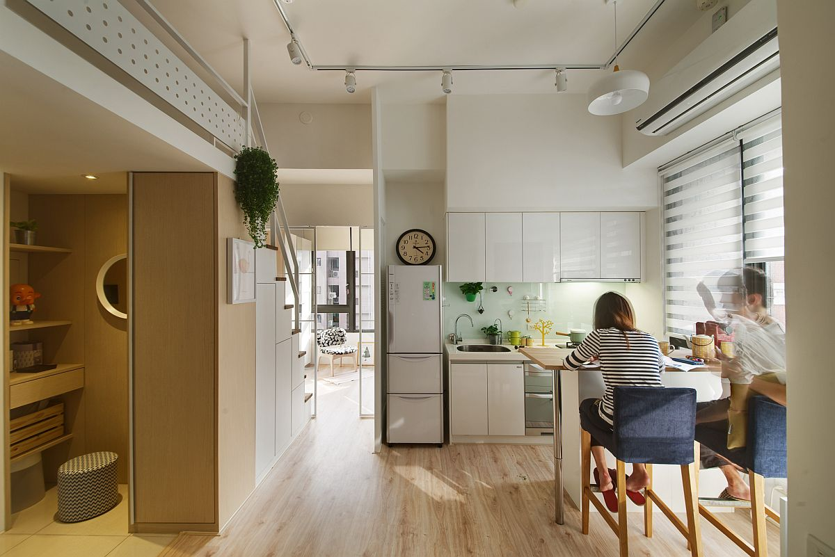 Open plan living brings together kitchen and dining inside the small apartment